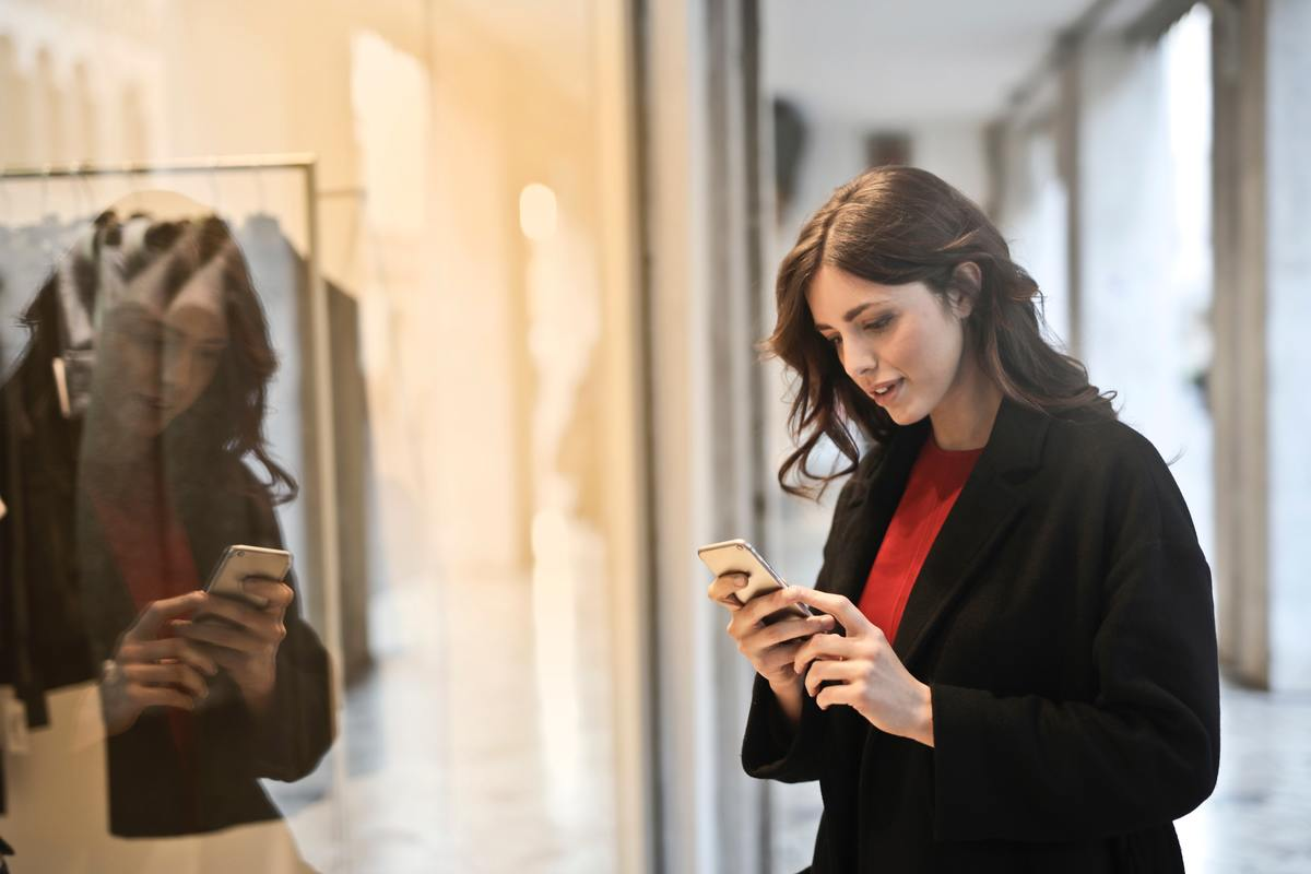 close-up-photo-of-woman-in-black-coat-using-smartphone-787929