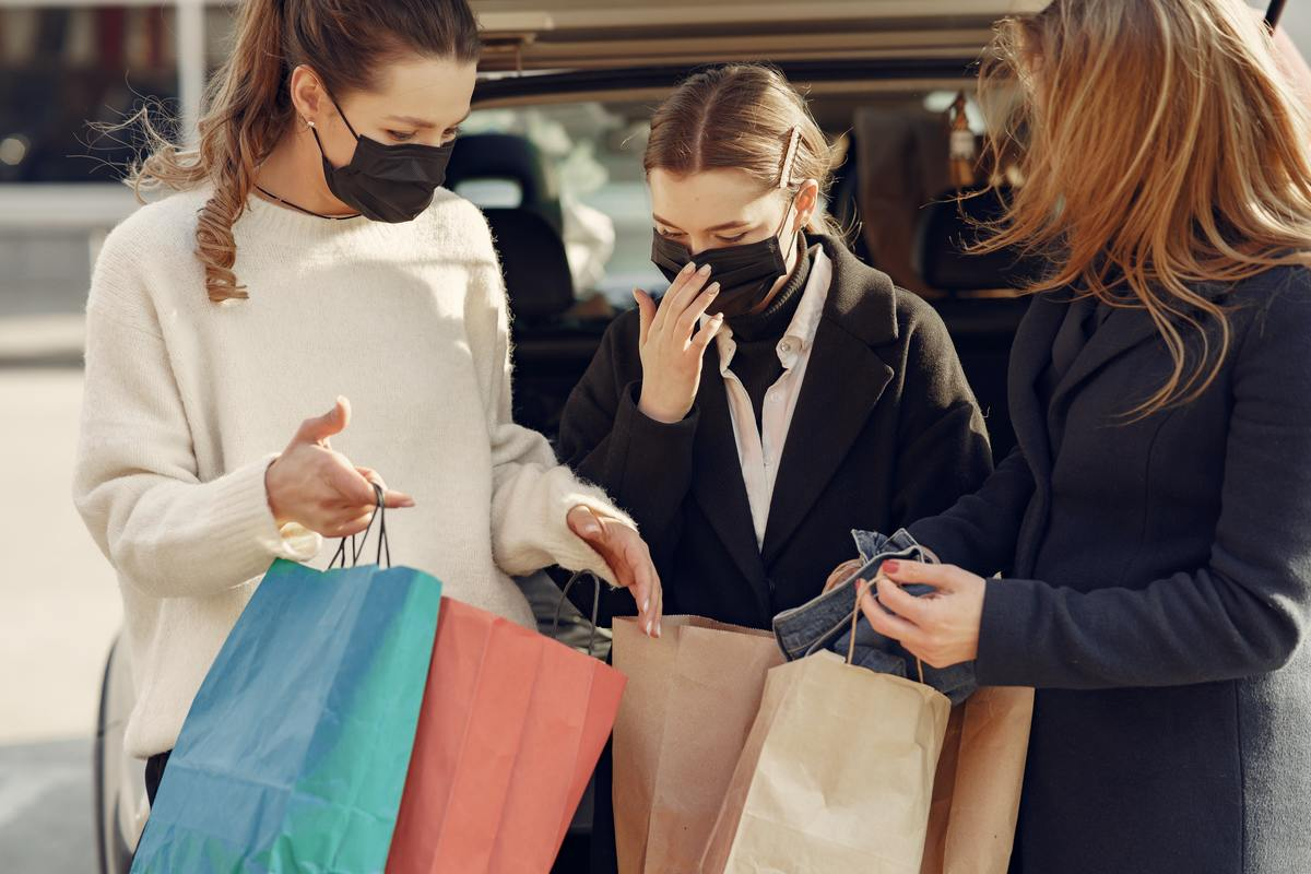 friends-showing-to-each-other-purchases-in-paper-bags-4005062