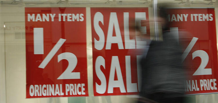 Sale signage on a store front facing a busy street