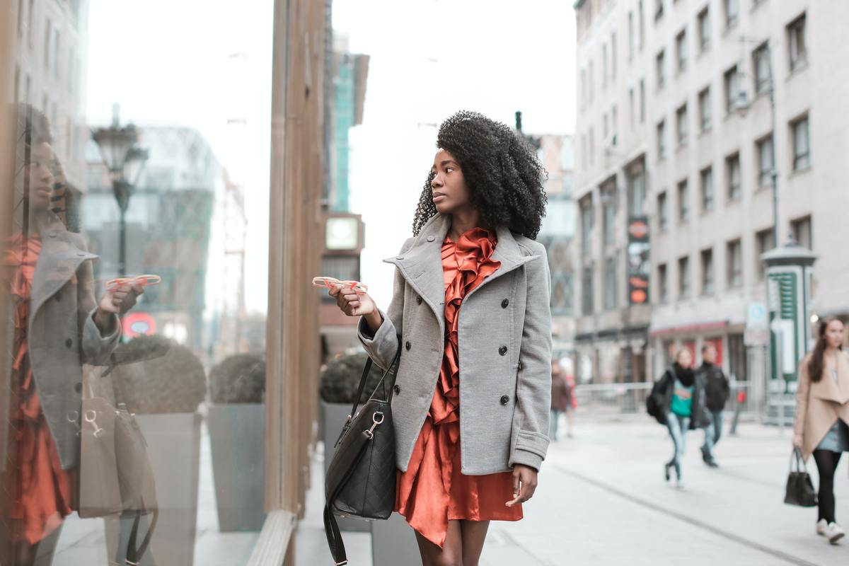 selective-focus-photo-of-woman-in-gray-coat-walking-by-store-3763124